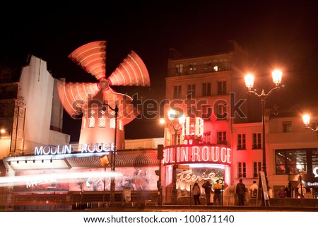 PARIS - MARCH 6: The Moulin Rouge at night, on March 6, 2012 in Paris, France. Moulin Rouge is a famous cabaret built in 1889 by Joseph Oller. People gather before show starts to get tickets.