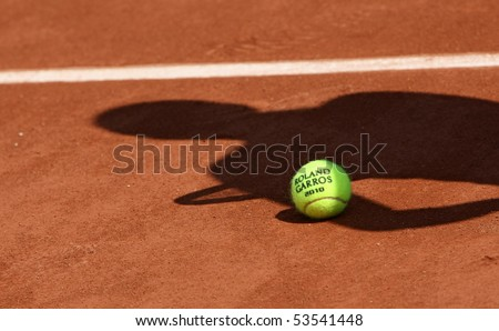 PARIS - MAY 20: Official ball of the French Open Grand Slam tennis tournament with the shadow of a tennis player on the clay clourt of Roland Garros on May 20, 2010 in Paris, France.