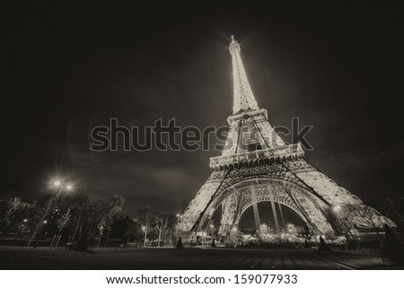 PARIS - NOV 30: Tourists walk underneath Eiffel Tower at dusk, November 30, 2012 in Paris. The Eiffel tower is the highest monument and also most visited monument of France