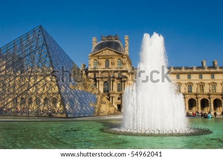 PARIS - OCTOBER 07: Famous glass pyramid and big fountain in front of Louvre Museum (former Royal Palace) October 07, 2007 in Paris France. The Louvre Museum is the most visited monuments in France. - stock photo