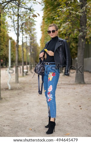 PARIS - OCTOBER 1, 2016: Stylish European woman with blue jeans during Paris Fashion week. With Fashion week in New York, London and Milan, they are the four biggest fashion events in the world.