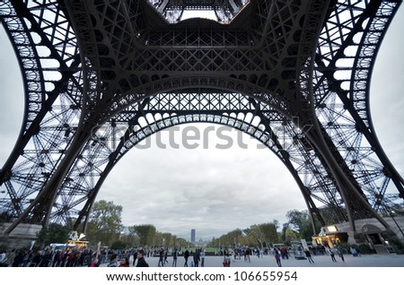 PARIS - OCTOBER 3: Tourists walk beneath Eiffel Tower in the evening of October 3, 2011 in Paris. Eiffel Tower is the most popular attraction of Paris, the most visited city in the world.