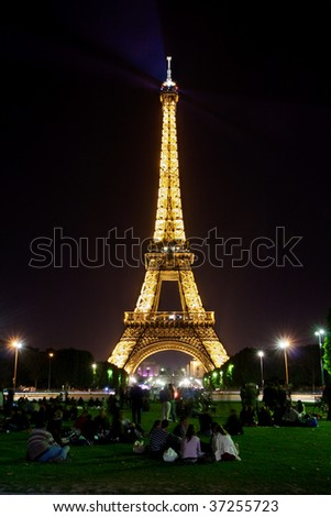 PARIS - SEPTEMBER 12: Illuminated Eiffel Tower at night and people on the Champs de Mars. The popular place for people for romantic evenings. September 12, 2009 in Paris, France. - stock photo
