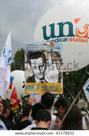 "PARIS - SEPTEMBER 23: Students carry a poster 'Sarkozy gives 15 million for the rich and for the students..."" at the strike against raise of the retirement age on September 23, 2010 in Paris, France"