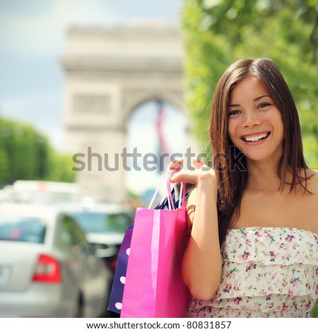 Paris shopping woman tourist on Champs-e?lysees with Arc de Triomphe in the background carrying shopping bags outside in Paris. Pretty Asian Caucasian female model. - stock photo
