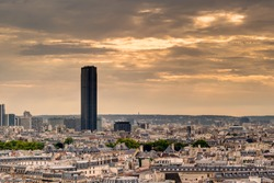 Paris skyline with Maine-Montparnasse Tower, France. Great Montparnasse Tour in summer evening. Dark Montparnasse Tower rises above the cityscape. Panorama of the city with Montparnasse skyscraper.