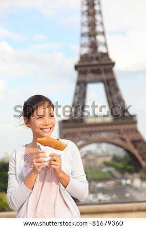 Paris woman and Eiffel Tower. Girl eating french crepe / pancake in front of Eiffel Tower, Paris, France. Mixed race Chinese Asian / Caucasian tourist.