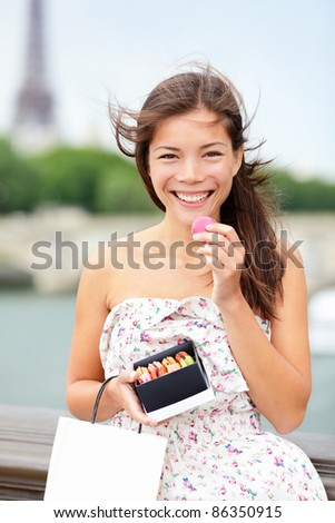 Paris woman eating macaroon with Seine and Eiffel Tower in background. Beautiful woman tourist holding macaroon box and shopping bag. stock photo