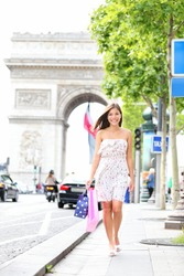 Paris woman shopping walking on Champs-Elysees with Arc de Triomphe in the background. Beautiful happy young woman tourist shopping during her travel in Paris, France