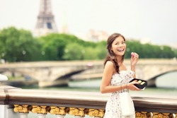 Paris woman smiling eating the french pastry macaron in Paris. Eiffel tower and Pont Des Invalides in the background. Cute beautiful mixed race Asian Caucasian female model.