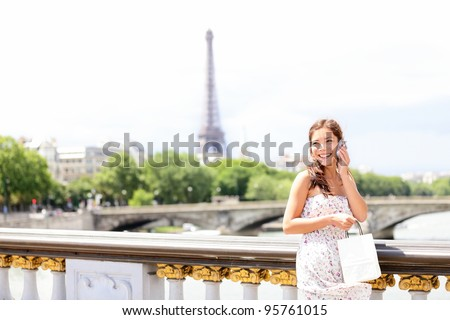 Paris woman talking on mobile phone / smart phone in Paris, France with Eiffel Tower in background. Cute beautiful multiracial Asian / Caucasian female model holding small shopping bag.