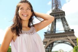 Paris woman tourist at Eiffel Tower smiling happy. Beautiful Caucasian Asian girl enjoying her Paris travel.