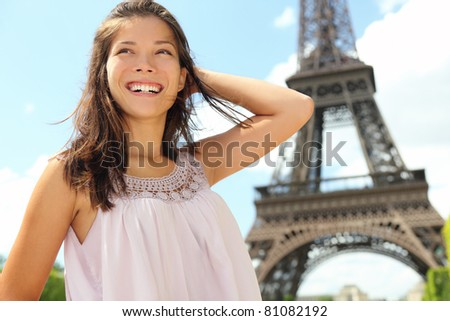 Paris woman tourist at Eiffel Tower smiling happy. Beautiful Caucasian Asian girl enjoying her Paris travel.