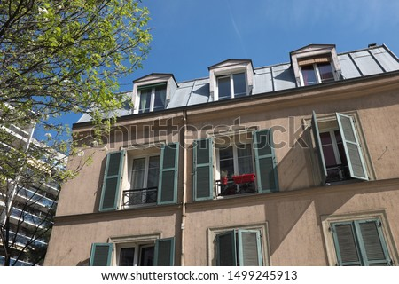 Parisian ancient facades with trees and blue sky. Roof of zinc.