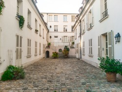 Parisian courtyard. Censier street, 5th arrondissement, Paris, France. Beautiful shot of a typical complex courtyard in the french capital. Stone pavement. First floor.