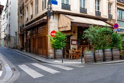 Parisian street with tables with tables of cafe in Paris, France. Architecture and landmark of Paris. Cozy Paris cityscape