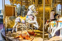 Parisian-style merry-go-round with the horses in the foreground. Fun concept for kids
