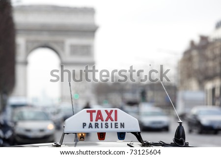 Parisian taxi on avenue des champs-elysees, with the Arc de Triomphe and traffic in the background