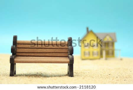 Park Bench on Sand With House in Background, Shallow DOF