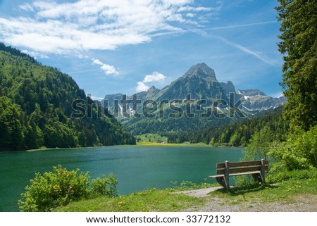 Park bench on shore of mountain lake
