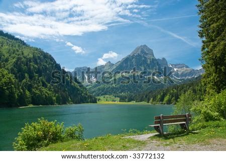 Park bench on shore of mountain lake