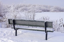 Park bench overlooking a lake in winter