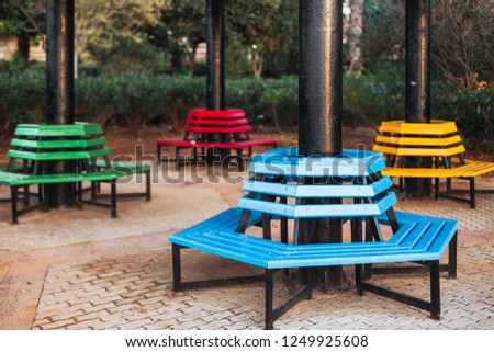 Park colored benches located around the column. Blue, yellow, green and red