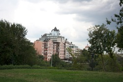 Park hill lawn on a summer day with urban buildings under cloudy sky on the background