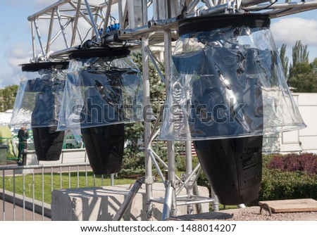 Park is installing stage lighting for street scene. Lamps covered with transparent protective covers. #1488014207