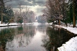 Park of Monza after a snowstorm with the Pond frozen, and the footpath covered with snow. Monza, Lombardy, Italy