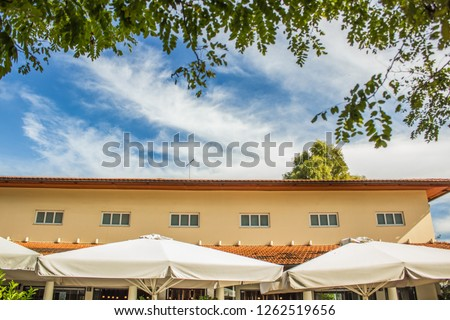 park outdoor garden environment of cafe restaurant patio space with umbrellas near building in summer clear fresh weather time #1262519656