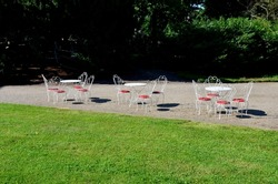 Park seating at a patisserie made of white painted wires bent into a shell shape. red leather cushions. chairs and tables on the sand square by the road.