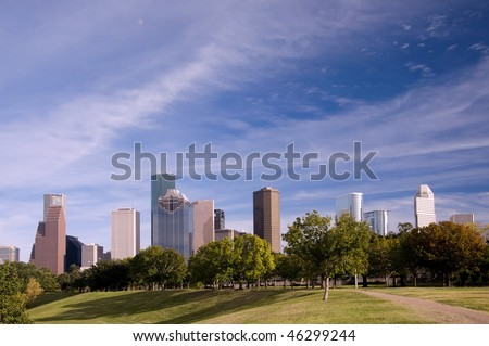 Park view of the Houston skyline with blue sky and clouds.