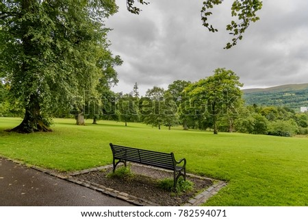 park with paths and benches on green and wooded lawns
