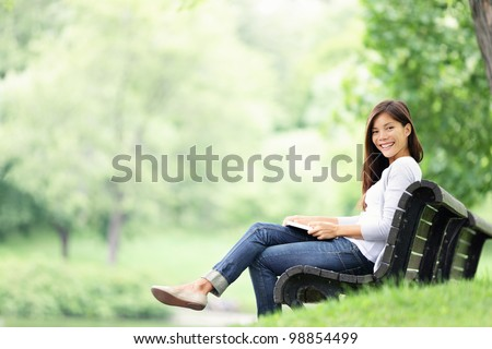 Park woman reading book on bench smiling happy at camera. Pretty young multicultural woman enjoying spring in park.