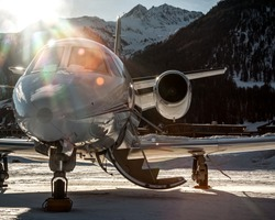 Parked at Samedan Engadin Airport over snow park at the last light of day. Private bizjet airplane used by businessmen, VIP and rich people to move around the world.