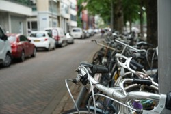 Parked bicycles along the street in Rotterdam, Netherlands. There are parked cars on the other side of the street there are parked cars. Photo taken with selective focus.