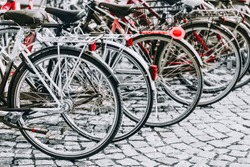 Parked Bicycles On Sidewalk. Bike Bicycle Parking In Big City. Red, Black, White and Red Colors Photo.
