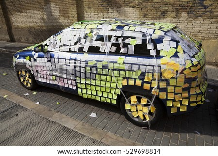Parked car covered by small stick color papers. Valencia, Spain.