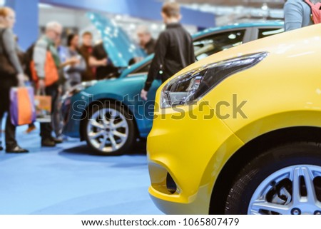 Parked Colorful Brand New Cars. Car Dealership For Sale in Fair Event. Gathering of People for Autos Entertainment or Commercial Activities. Transportation Industry Concept with Person in Photo. #1065807479