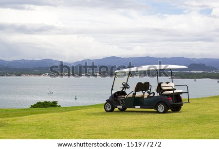 parked golf cart facing water reservoir with dramatic cloudy sky