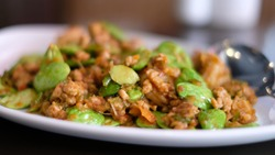 Parkia stirred fry on a plate with blurred spoon
