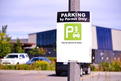 Parking by permit only sign. Pay for permit at meter sign in parking lot against blurred cars and building background. Copy space.