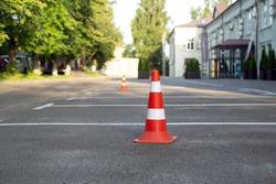 parking cone on the asphalt. Plastic orange parking cone standing in the street. Orange and white road cone for parking, selective focus. Parking cones