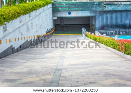 Parking entrance with signals, asphalt ascent and white sing board. #1372200230
