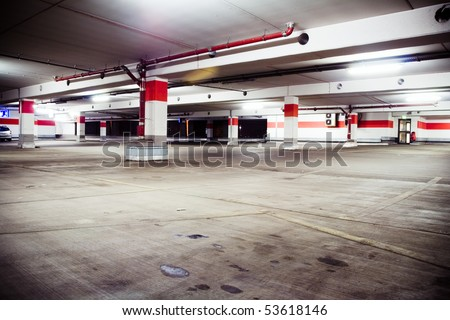 Parking garage, grunge and dirty underground interior. Neon light in bright industrial building.
