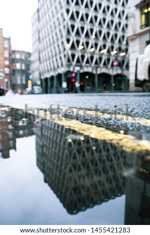 Parking garage in London, England, with weird walls. Picture taken through a puddle of water