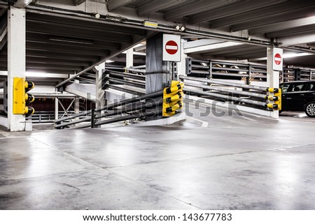 Parking garage lot, urban scene at night in city and cars on parking lot. Dark and grunge construction interior.