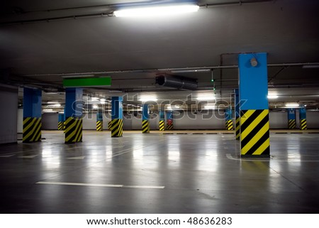 Parking garage of shopping center, underground interior. Neon light in bright industrial building.