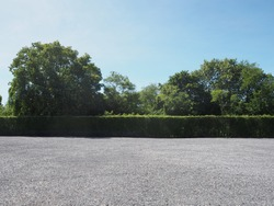 Parking lot sprinkled with gravel bush green tree blue sky nature background